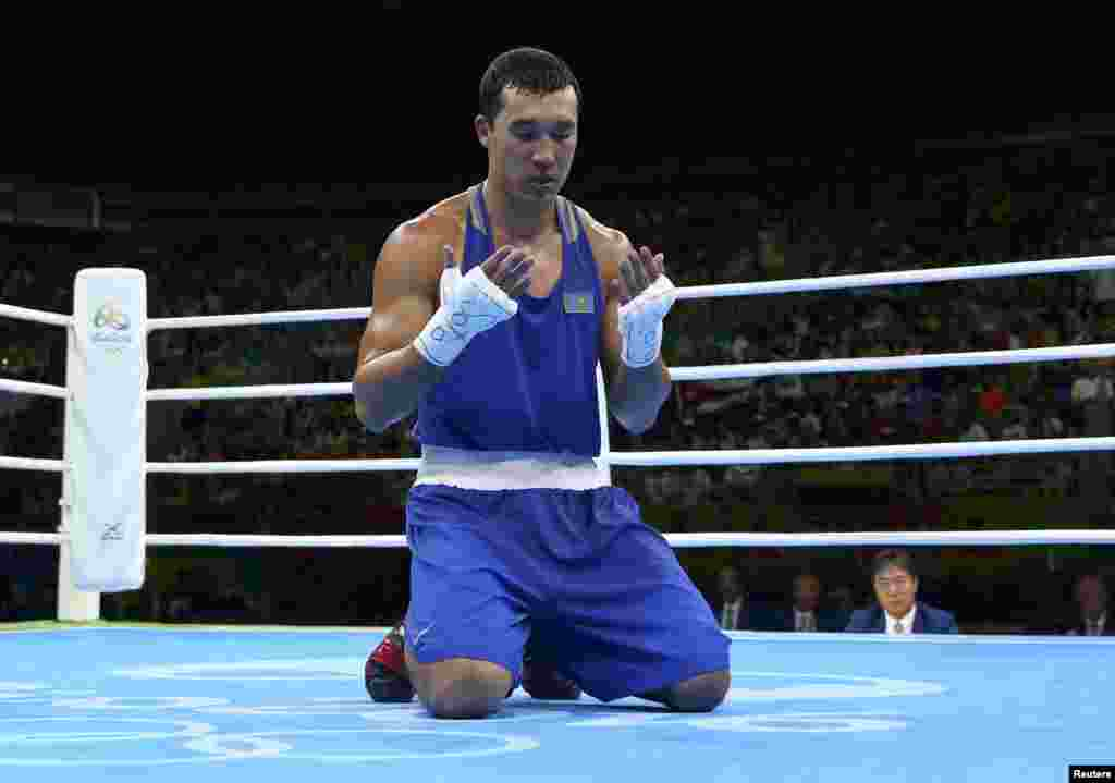 Adilbek Niyazymbetov of Kazakhstan prays on the ring before competing in the light heavyweight boxing final. He took home silver after being defeated by Cuban Julio Cesar La Cruz.