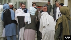 Kandahar Governor Tooryalai Wesa (right, facing camera) greets Taliban fighters as they peacefully surrender arms during a meeting with Afghan government officials as part of the government's peace and reintegration process in Kandahar in 2011.