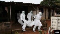 Дәрігерлер Эбола вирусынан қайтыс болған адамның денесін әкетіп барады. Либерия, 6 тамыз 2014 жыл.