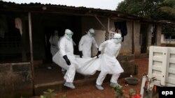Дәрігерлер Эбола вирусынан көз жұмған науқасты әкетіп барады. Либерия, Монровия, 6 тамыз 2014 жыл.