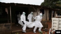 پرستاران لیبریایی در حال انتقال جسد یک فرد مبتلا به بیماری ابولا برای خاکسپاری.