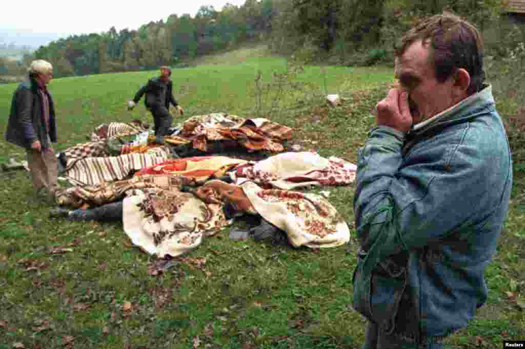The stench of death. An ethnic Croatian man holds his nose as he helps collect the decomposing bodies of 15 people left to rot in a meadow in northwest Bosnia, on October 16, 1995. Numerous mass grave sites were discovered in the wake of the Serb retreat from northwest Bosnia.