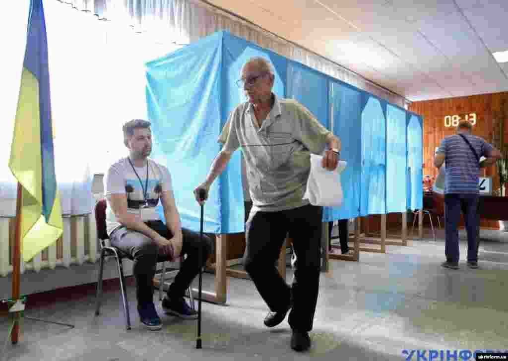Літній чоловік несе бюлетень на виборчій дільниці у місті Вишневе, Київської області