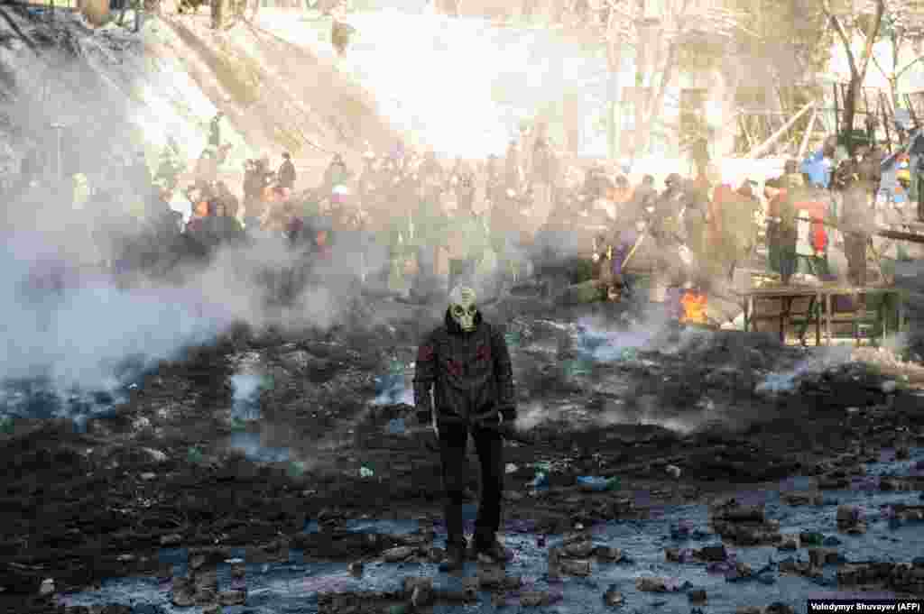 A protester wearing a gas mask walks through smoking rubble.