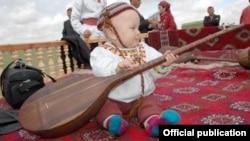 Türkmen çagasynyň dutar çalmaga höwes edýän pursady.