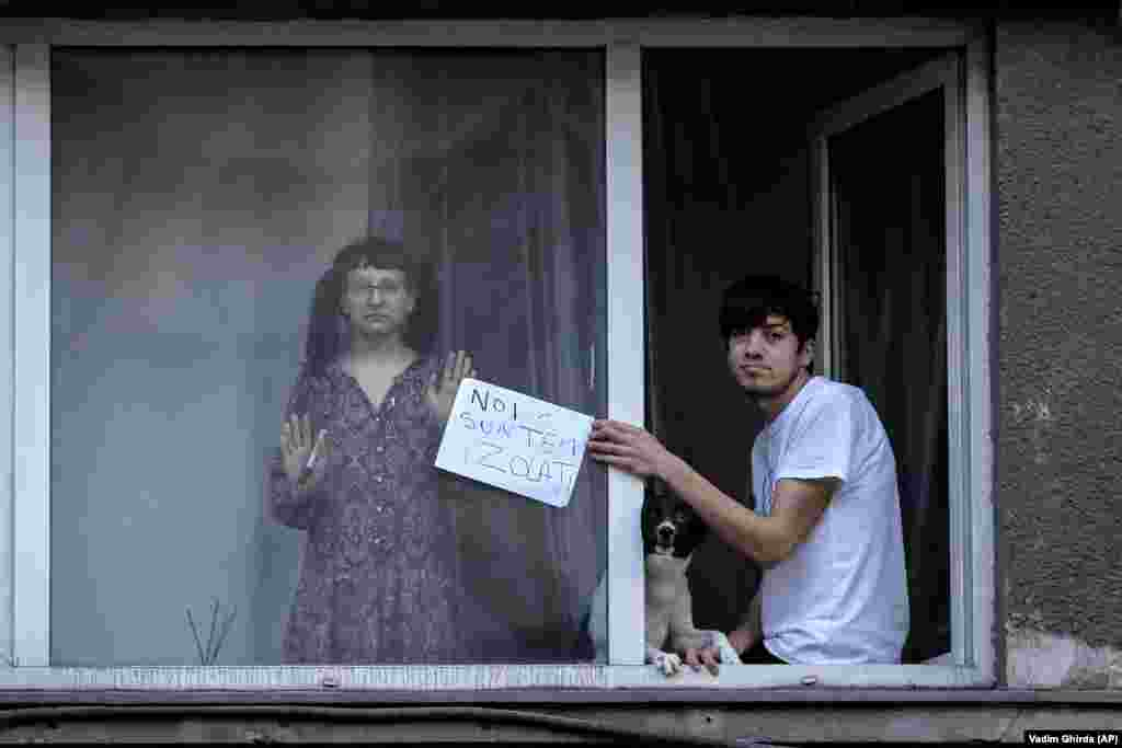 """A young man holds up a sign that reads: """"We are in isolation,"""" while watching the Bucharest protest from his window."""
