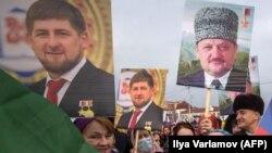Люди держат фотографии первого президента Чечни Ахмада Кадырова и главы Чеченской республики Рамзана Кадырова во время митинга в центре Грозного, 22 января 2016 г.