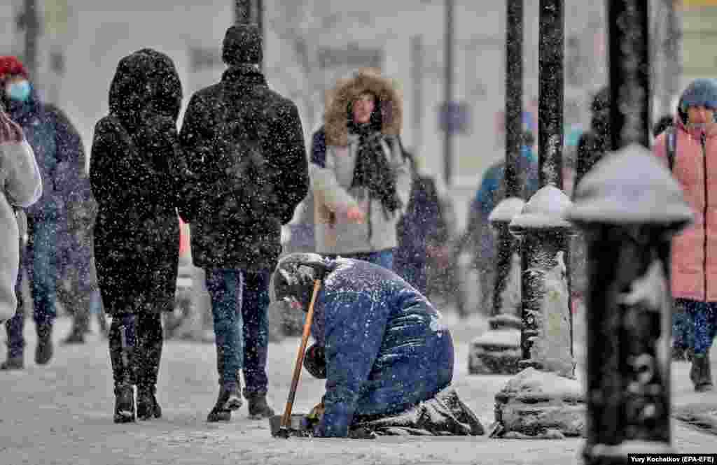 An elderly woman begs on a street during snowfall in Moscow. (epa-EFE/Yury Kochetkov)