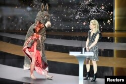 Actrița Corinne Masiero, îmbrăcată pentru scurt timp într-un costum de măgar, peste o rochie pătată de sânge, în timpul ceremoniei la Gala Premiilor Cesar