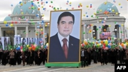 Crowds carry a giant portrait of President Gurbanguly Berdymukhammedov during Turkmen Independence Day celebrations in Ashgabat on October 27, 2009.
