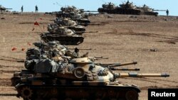 Turkish Army tanks take up position on the Turkish-Syrian border on October 6.
