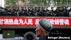 Уйгур на фоне грузовика с бойцами спецназа, Синьцзян.