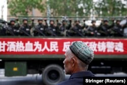 A Uyghur man looks on as a truck carrying paramilitary policemen travels along a street during an antiterrorism oath-taking rally in Urumqi, Xinjiang Uighur Autonomous Region, in 2014.