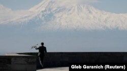 Маж положува цвеќе во меморијалниот центар во Ереван на одбележување на годишнината од масакрот врз Ерменците