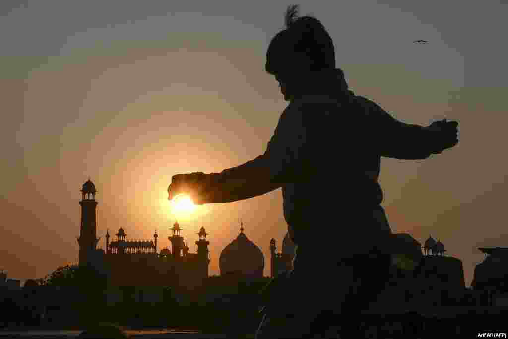 A boy plays near the historic Badshahi Mosque at sunset in Lahore, Pakistan. (AFP/Arif Ali)