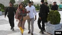 Полицей әйелге киіміне қатысты ескерту жасап келеді. Тегеран, 11 маусым 2012 жыл. (Көрнекі сурет)