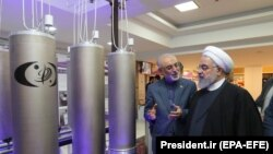 Iranian President Hassan Rohani and head of Iran's nuclear technology organization Ali Akbar Salehi (2-R) visit a nuclear facility during the National Nuclear Technology Day in Tehran, April 9, 2019