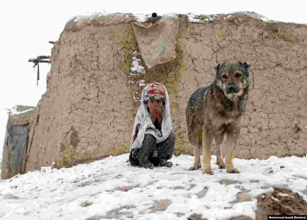 An internally displaced Afghan boy sits outside his shelter during a snowfall in Kabul. (Reuters/Mohammad Ismail)