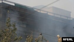 Afghan firefighters work to contain a fire at the UN guesthouse in Kabul following the militant attack.
