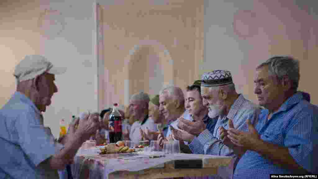 Мужчины читают молитву перед едой