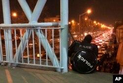 Іранський поліцейський спостерігає за протестувальниками, які зібралися, щоб вимагати покарання винних у збитті українського літака іранськими військовими. Тегеран, 12 січня, 2020 року
