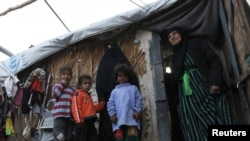Iraqis stand outside a shelter at Umm Al-Banin camp, one of the UNHCR's 94 camps for internally displaced people, in Baghdad in January.