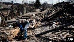 Мужчына на згарэлым пасьля абстрэлу даху дому ў Данецку