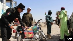 Afghan policemen search travelers at a checkpoint in Lashkar Gah in Helmand Province (file photo)