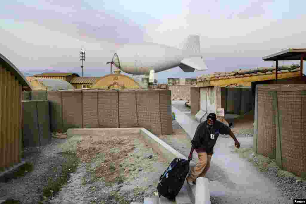 A contractor drags his bag out of a housing complex at Forward Operating Base Gamberi, which remains part of the ongoing Operation Resolute Support in Afghanistan's Laghman Province. (Reuters/Lucas Jackson)