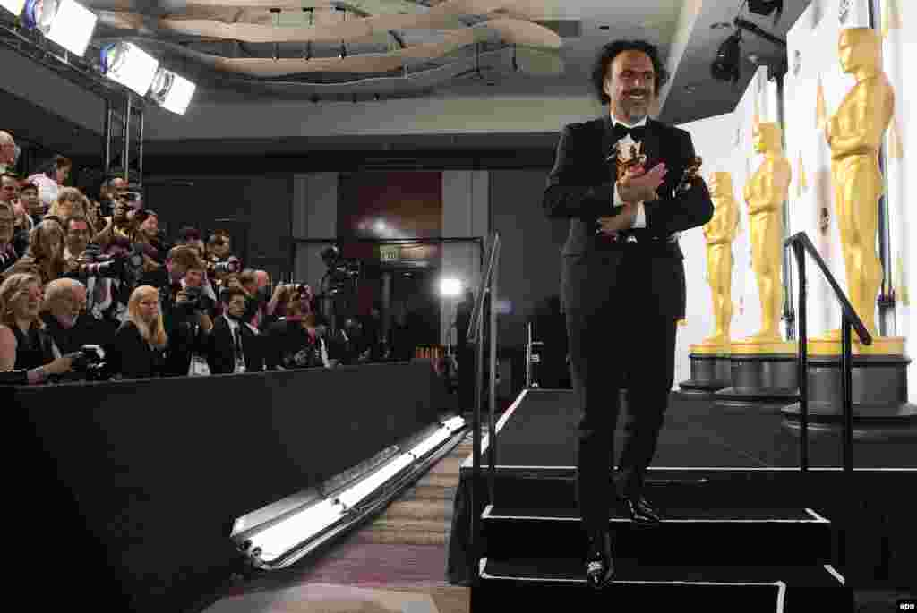 Weighed down with awards - Alejandro G. Inarritu poses with his Academy Awards for Best Picture, Best Director and Best Original Screenplay for Birdman. The film also won the Best Cinematography prize.