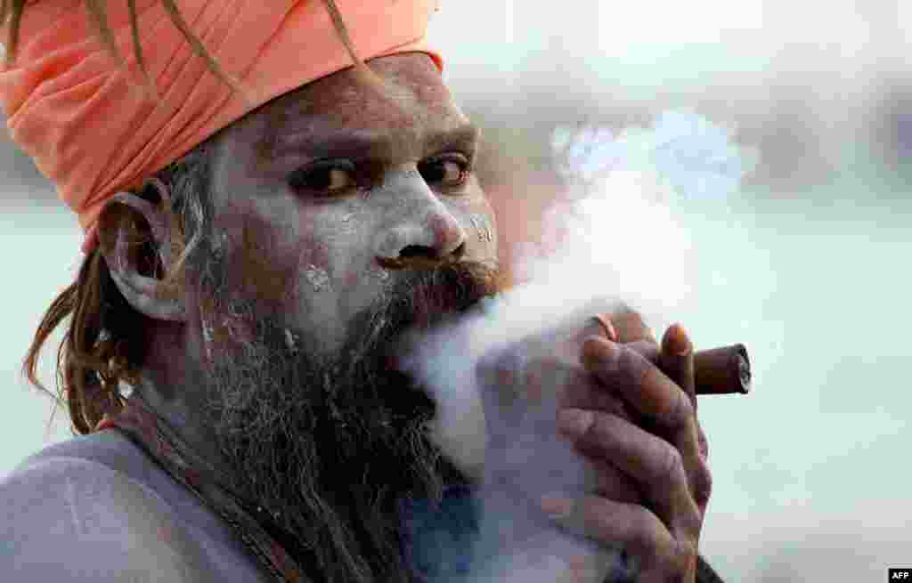 "An Indian holy man smokes a ""chillum"" as he prepares for the upcoming Kumbh Mela festival in Allahabad, India. The Hindu festival is the largest gathering of people for a religious purpose in the world. Tens of millions of people gather for the multiweek occasion. (AFP/Sanjay Kanojia)"