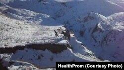 Мужчина в труднодоступной горной местности тянет осла, верхом на котором сидит беременная женщина. Снимок британской благотворительной организации HealthProm.