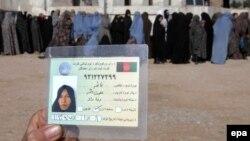 Жінка-афганка показує своє посвідчення для голосування, інші жінки (на задньому плані) стоять у черзі, щоб отримати свої посвідчення, Герат, 26 лютого 2014 року