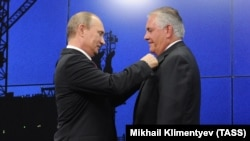 Then-ExxonMobil chief Rex Tillerson receives a state friendship award from Russian President Vladimir Putin in St. Petersburg in 2013.