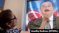 An Azerbaijani woman with an election poster for incumbent President Ilham Aliyev