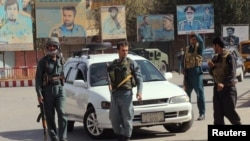 Afghan policemen keep watch in the downtown of the city of Kunduz on October 3.