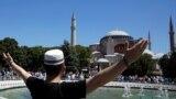 Мужчина радуется перед Айя-Софией на фоне толпы людей, ожидающих открытия древнего сооружения для пятничной молитвы.