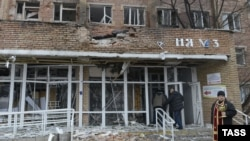 A priest stands in front of a hospital destroyed after shelling between Ukrainian forces and pro-Russian separatists in the eastern city of Donetsk on January 19.