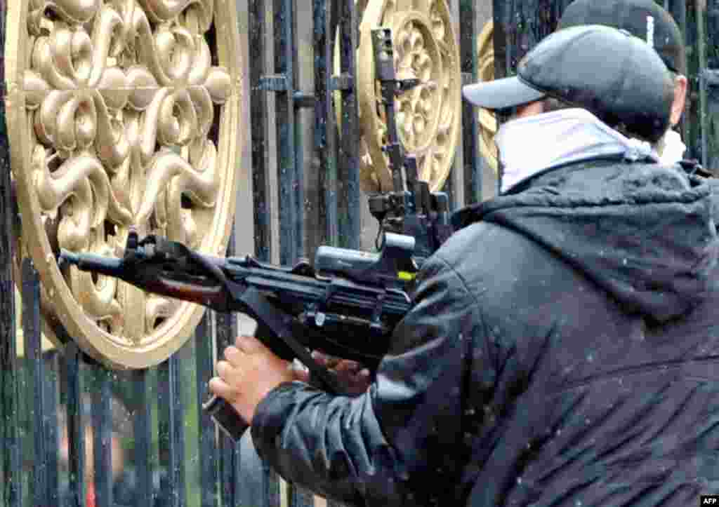 A Kyrgyz opposition supporter fires an automatic weapon near the main government building.