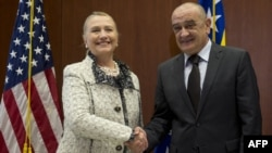 Bosnian Prime Minister Vjekoslav Bevanda (right) greets U.S. Secretary of State Hillary Clinton at the U.S. Embassy in Sarajevo.