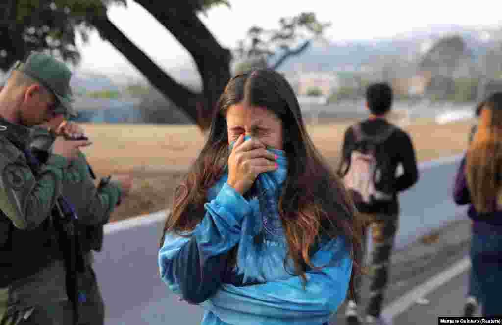 A woman reacts to tear gas near the Generalisimo Francisco de Miranda Air Base in eastern Caracas.