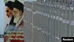 A poster of Iran's Supreme Leader Ayatollah Ali Khamenei (right) and the late Ayatollah Ruhollah Khomeini is seen next to a bank of centrifuges in what state TV described as a facility in Natanz.