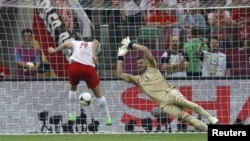 Poland's Robert Lewandowski (left) scores the first goal of Euro 2012 in the opening match against Greece.