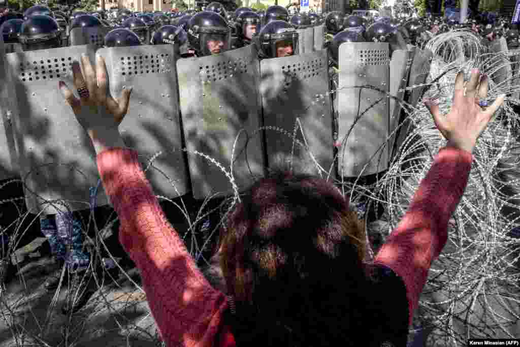 A woman gestures as Armenian special police forces block a street during an opposition rally in central Yerevan on April 16. Thousands of people rallied against a move by former President Serzh Sarkisian to maintain what they see as a chokehold on power after he became prime minister. (AFP/Karen Minasian)