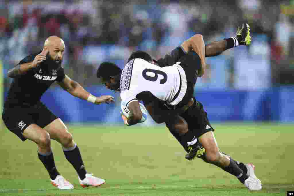 Jerry Tuwai of Fiji (front) fights for the ball with Akira Ioane of New Zealand during a men's rugby sevens quarterfinal match. Top-ranked Fiji defeated New Zealand 12 to 7.