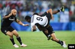 Фиджи (ақ формада) мен Жаңа Зеландияның командалары арасында регбиден ширек финалдық кездесу.