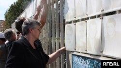 Nesrete Kumnova uklanja sliku sina koja je već godinama bila zakačena na ogradi Skupštine Kosova. 30. avgust 2012.
