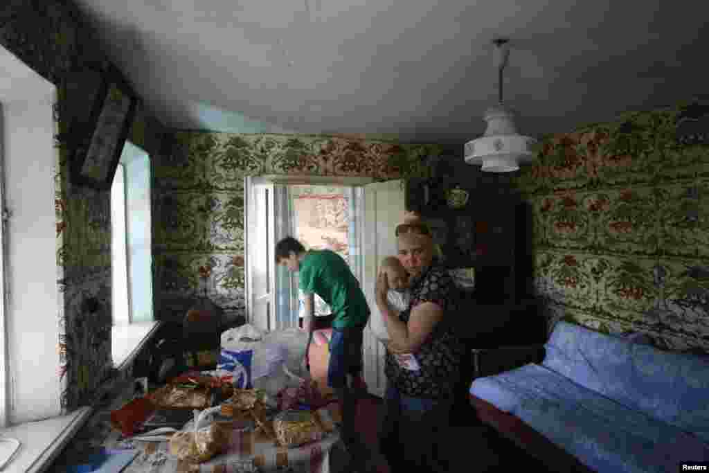 A family settles in their temporary accommodation in the town of Nyzhnya Krynka in eastern Ukraine.