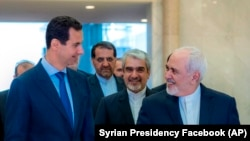 Syrian President Bashar Assad, left, speaks with Iranian Foreign Minister Mohammad Javad Zarif, right, in Damascus, April 16, 2019