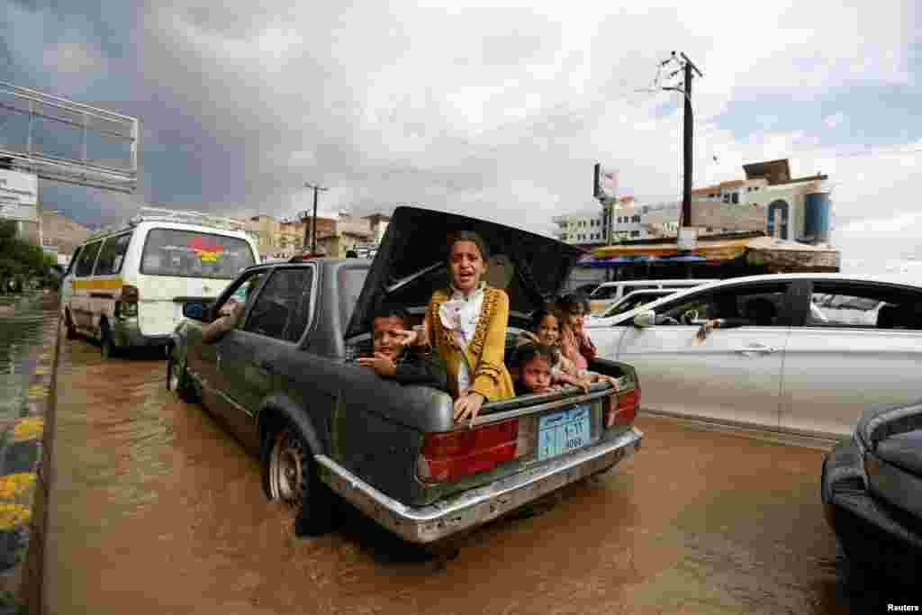 Children ride in the trunk of a car on a flooded street in Sanaa, Yemen. (Reuters/Khaled Abdullah)